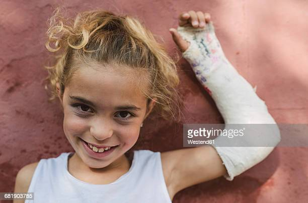 Portrait of smiling blond girl with plastered arm