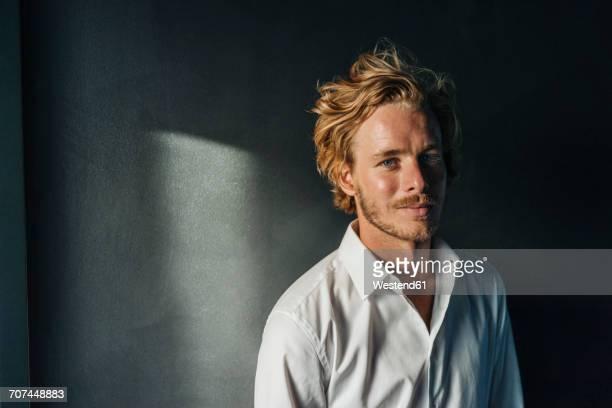portrait of smiling blond man wearing white shirt - schlagschatten stock-fotos und bilder