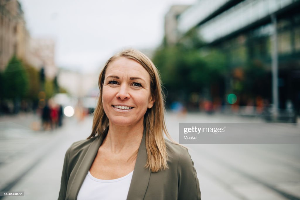 Portrait of smiling blond mature businesswoman standing on street in city : Stock-Foto