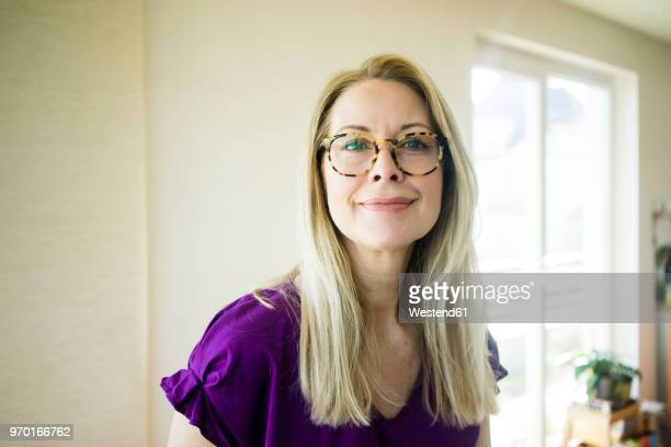 portrait of smiling blond mature woman wearing glasses - 45 49 jahre stock-fotos und bilder