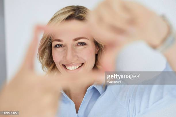 portrait of smiling blond woman building frame with her fingers while looking at viewer - women in see through shirts stock photos and pictures