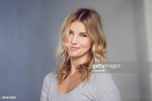 portrait of smiling blond woman in front of grey background - personas bellas fotografías e imágenes de stock