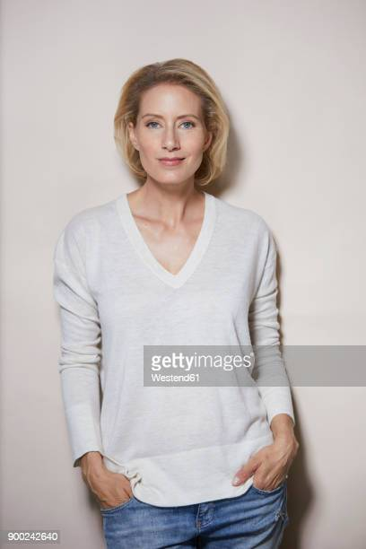 portrait of smiling blond woman in front of light background - 40 44 jaar stockfoto's en -beelden