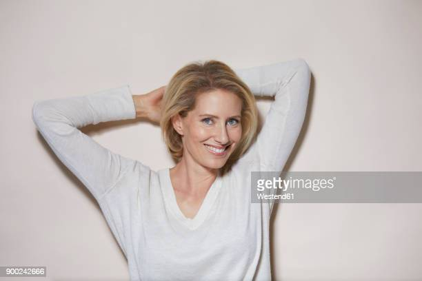 portrait of smiling blond woman in front of light background - one mature woman only stock pictures, royalty-free photos & images