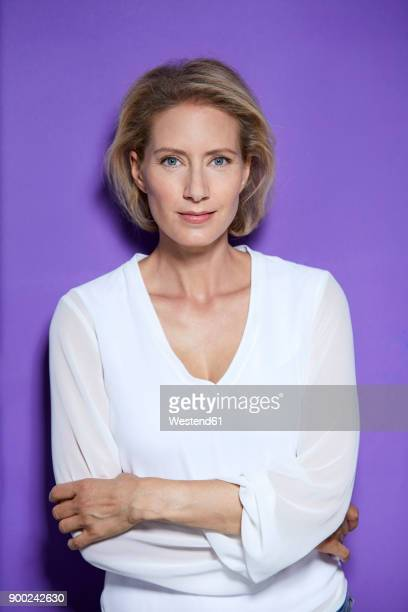 portrait of smiling blond woman in front of purple background - waist up stock pictures, royalty-free photos & images