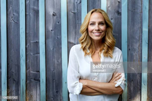 portrait of smiling blond woman in front of wooden wall - one mature woman only stock pictures, royalty-free photos & images