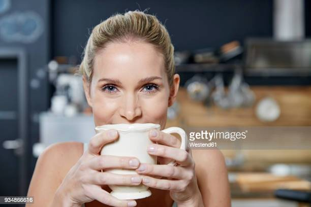 portrait of smiling blond woman in the kitchen holding coffee mug - mug stock pictures, royalty-free photos & images