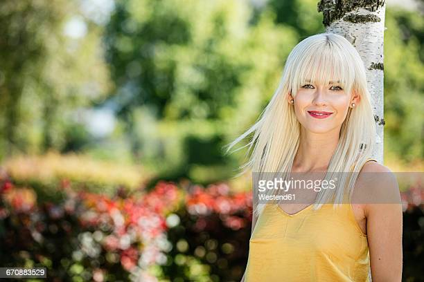 Portrait of smiling blond woman leaning against tree trunk