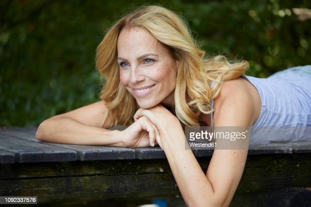 portrait of smiling blond woman lying on wooden jetty - one mature woman only stock pictures, royalty-free photos & images