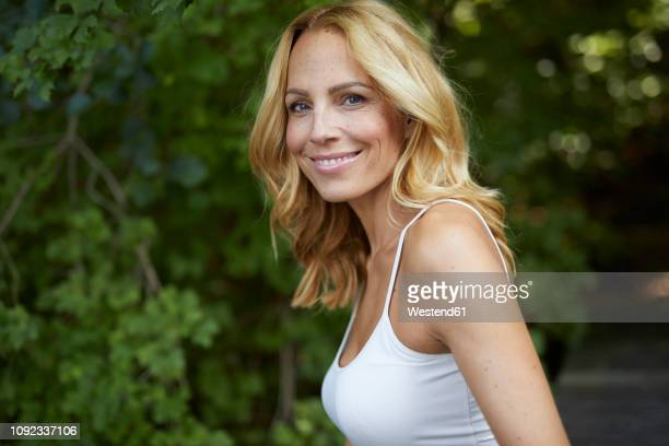 portrait of smiling blond woman outdoors - tank top stock pictures, royalty-free photos & images