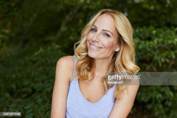 portrait of smiling blond woman outdoors - schöne menschen stock-fotos und bilder