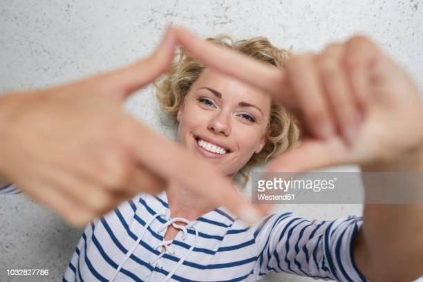 portrait of smiling blond woman shaping frame with her fingers - women wearing see through clothing stock pictures, royalty-free photos & images