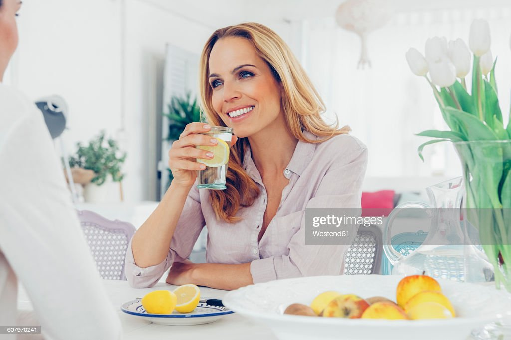 Portrait of smiling blond woman sitting at dining table communicating with her female friend : Stock Photo