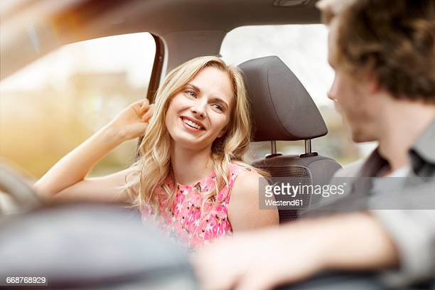 Portrait of smiling blond woman sitting on passenger seat in a car talking to her friend