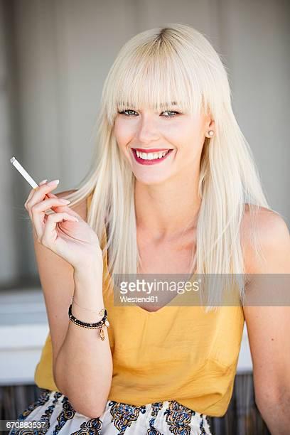 Portrait of smiling blond woman smoking cigarette