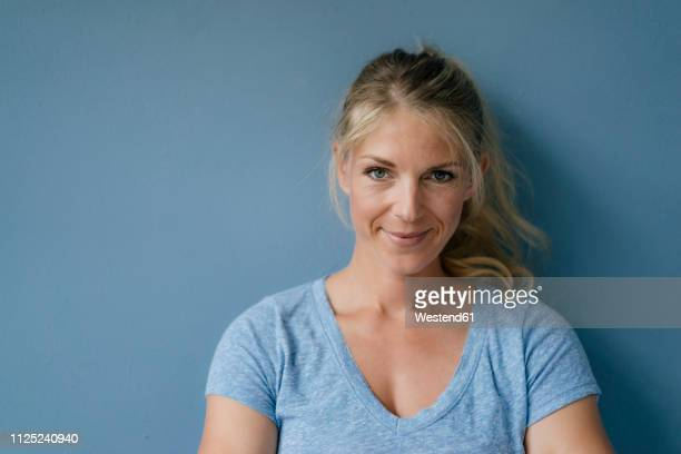 portrait of smiling blond woman standing at blue wall - einzelne frau über 30 stock-fotos und bilder