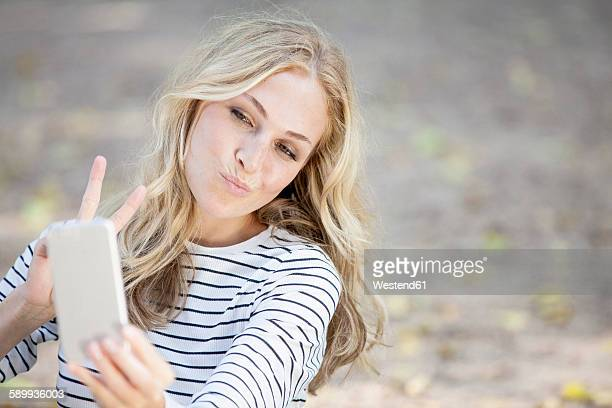 Portrait of smiling blond woman taking a selfie with her smartphone
