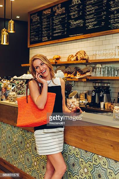 Portrait of smiling blond woman telephoning at counter in a coffee shop