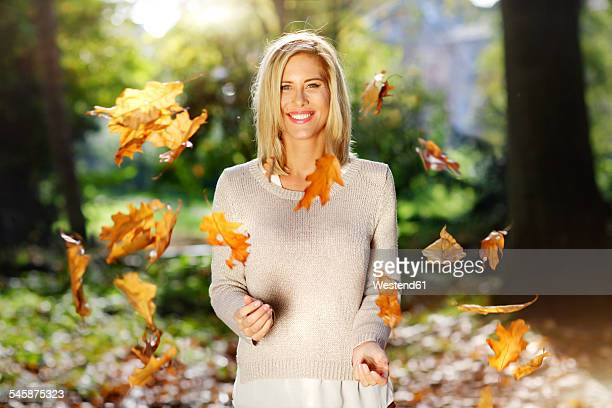 Portrait of smiling blond woman throwing with autumn leaves