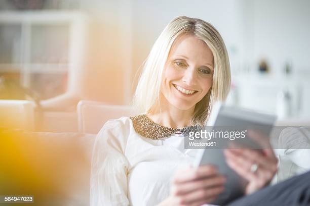 Portrait of smiling blond woman using mini tablet at home