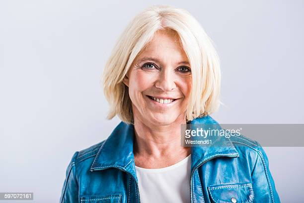 Portrait of smiling blond woman wearing blue leather jacket
