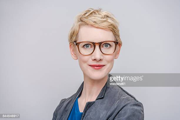portrait of smiling blond woman wearing glasses in front of grey background - めがね類 ストックフォトと画像