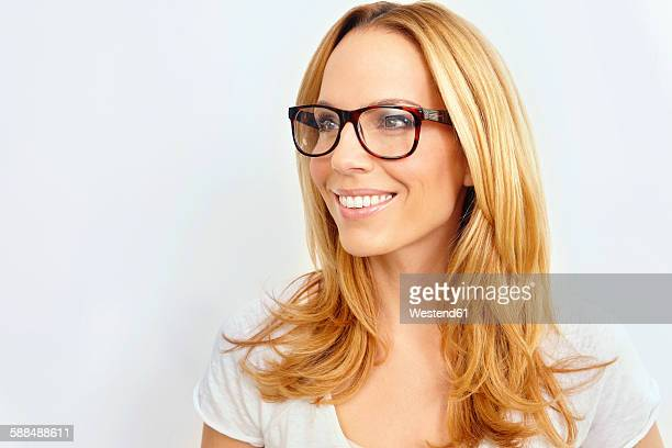 Portrait of smiling blond woman wearing glasses in front of white background