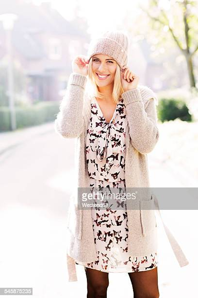 Portrait of smiling blond woman wearing patterned dress, cardigan and wool cap