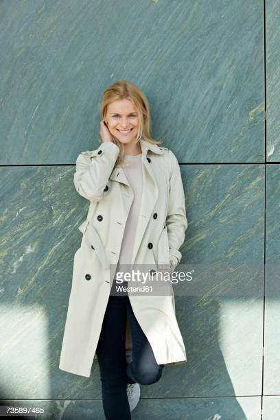Portrait of smiling blond woman wearing trench coat leaning against wall
