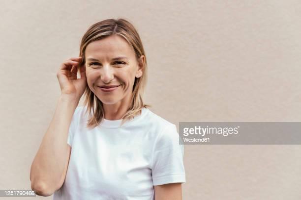 portrait of smiling blond woman wearing white t-shirt in front of light wall - frauen zwischen 30 und 40 stock-fotos und bilder