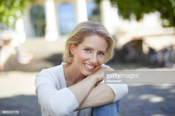 portrait of smiling blond woman with arms crossed - hoofd schuin stockfoto's en -beelden