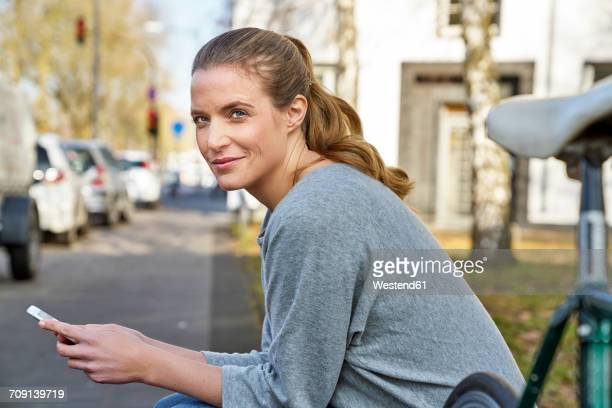 Portrait of smiling blond woman with cel phone