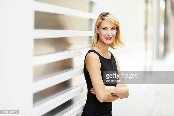 portrait of smiling blond woman with crossed arms - sleeveless stock pictures, royalty-free photos & images
