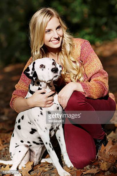 Portrait of smiling blond woman with Dalmatian in autumnal forest