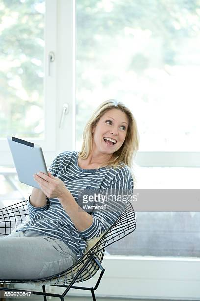 Portrait of smiling blond woman with digital tablet