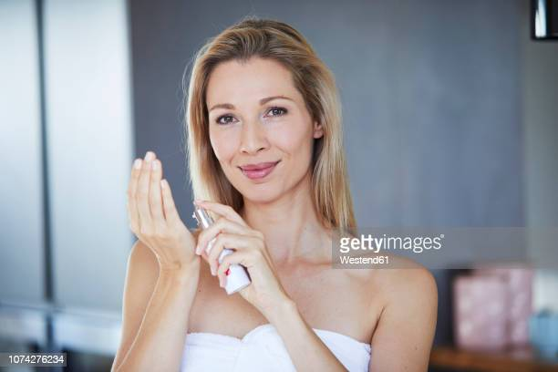 portrait of smiling blond woman  with dispender applying face cream - creme stock-fotos und bilder