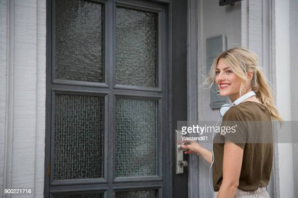 Portrait of smiling blond woman with headphones standing in front of entry door