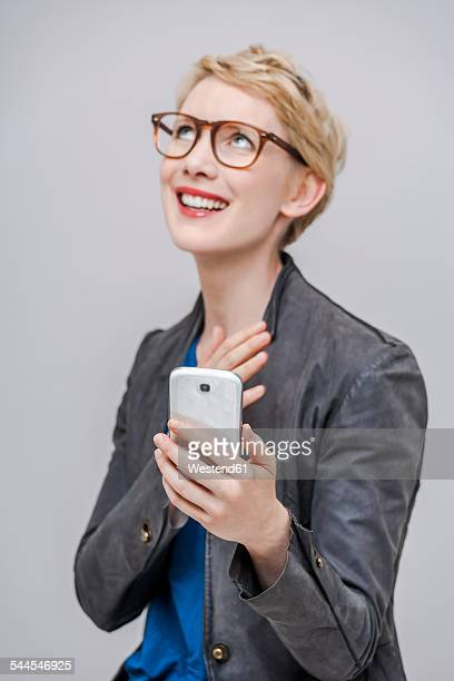 Portrait of smiling blond woman with her smartphone in front of grey background