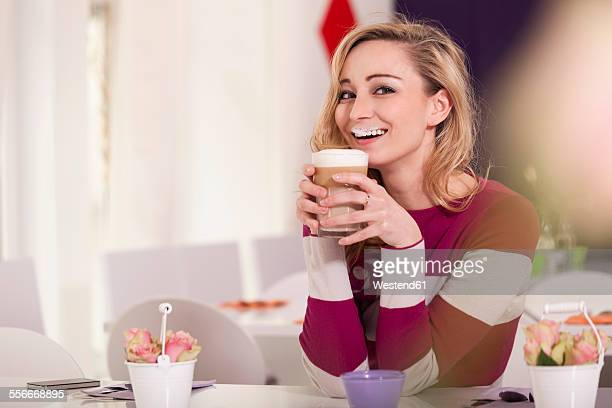 Portrait of smiling blond woman with milk moustache holding glass of Latte Macchiato