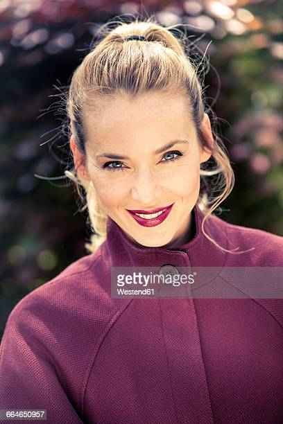 Portrait of smiling blond woman with ponytail