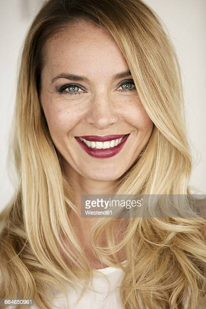 Portrait of smiling blond woman with red lips