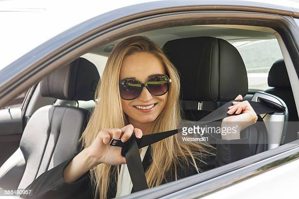 Portrait of smiling blond woman with sunglasses putting on safety belt in her car