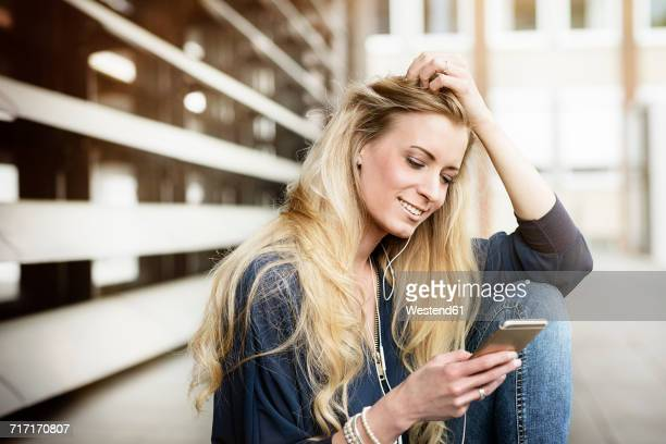 portrait of smiling blond young woman with earphones looking at cell phone - cabello largo fotografías e imágenes de stock