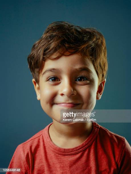 portrait of smiling boy against blue background - 4 5 anni foto e immagini stock