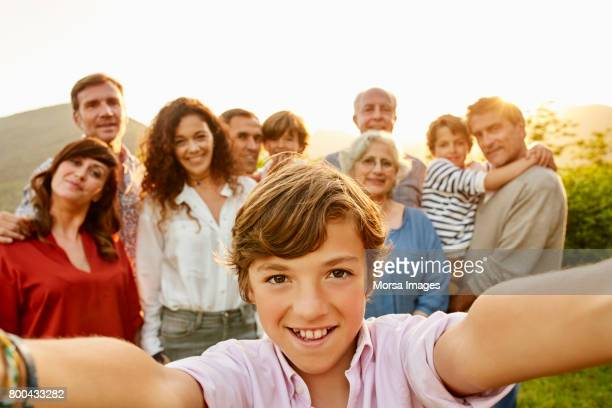 portrait of smiling boy against family in yard - multigenerational family stock photos and pictures
