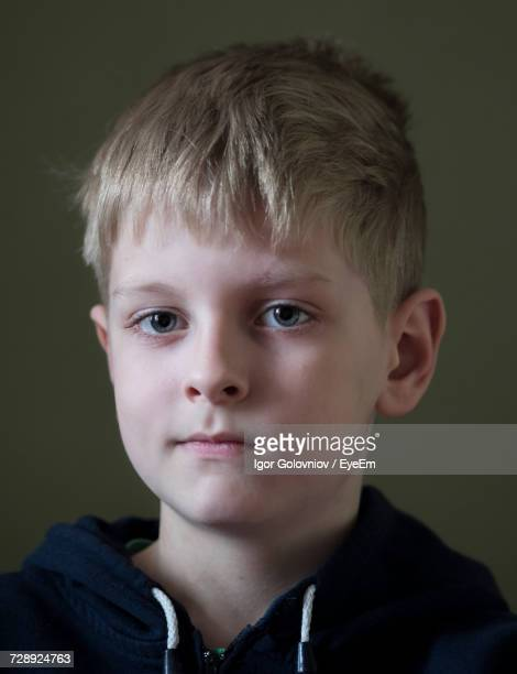 portrait of smiling boy against green background - igor golovniov stock pictures, royalty-free photos & images