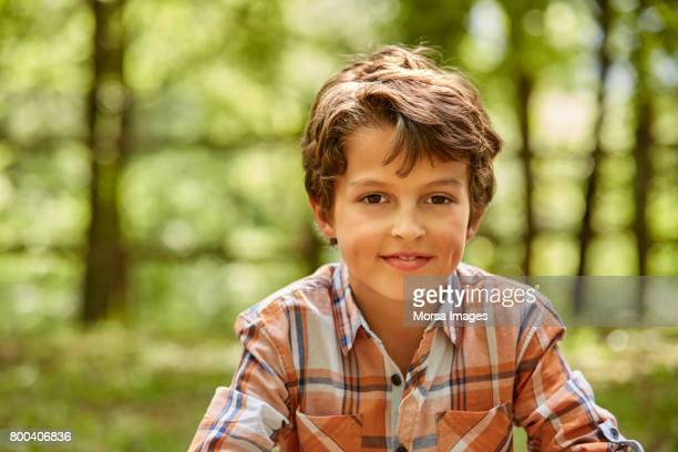 portrait of smiling boy against trees in forest - brown hair stock pictures, royalty-free photos & images