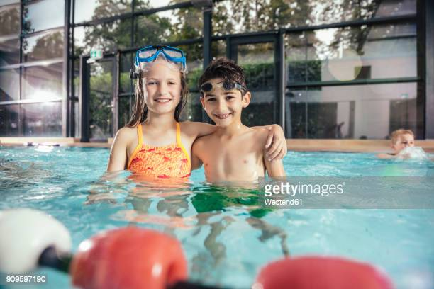 Portrait of smiling boy and girl in swimming pool