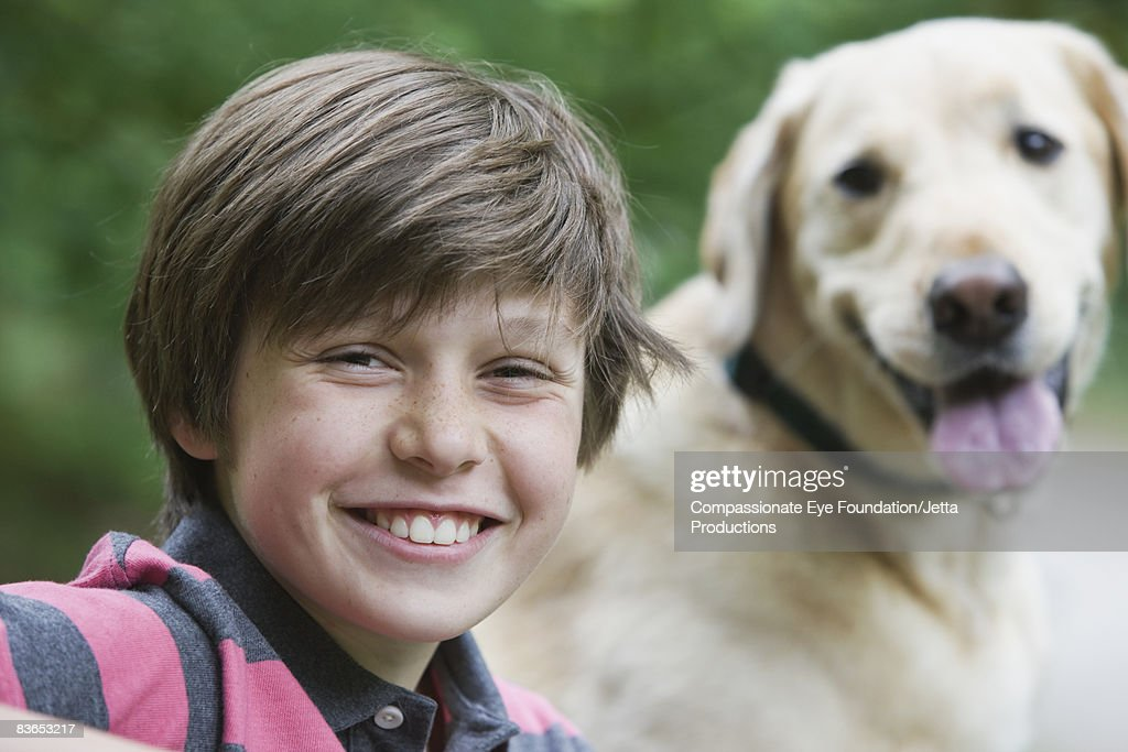 Portrait of smiling boy and his dog : Stock Photo