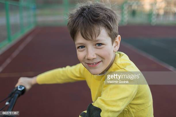 Portrait of smiling boy cycling in court